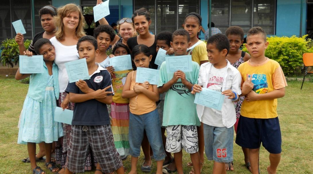 A group photo of a Projects Abroad volunteer with her students outside her volunteer teaching placement in Fiji
